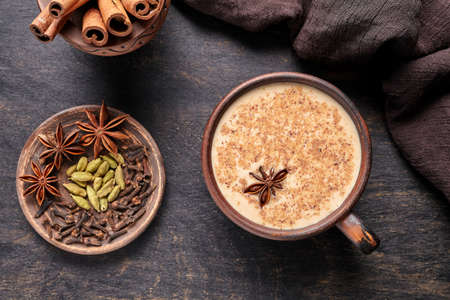 Masala tea chai latte traditional hot Indian sweet milk spiced drink, ginger, cinammon sticks, fresh spices blend, green cardamom, anise, organic infusion healthy wellness beverage in rustic clay cup