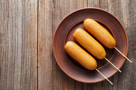 Corn dog traditional American corndog street junk food deep fried meat sausage snack treat coated in a thick layer of cornmeal batter on stick unhealthy eating on rustic wooden background table. Stock Photo