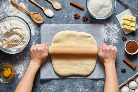 Dough bread, pizza or pie recipe homemade preparation. Female chef cook hands rolling dough with pin. Food ingridients flat lay on kitchen table. Working with pastry or bakery cooking. Top view