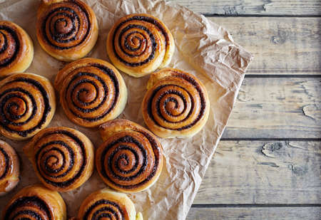 Freshly baked buns rolls with cinnamon and cocoa filling on parchment paper. Top view. Close-up. Kanelbulle - swedish Sweet Homemade christmas dessert. Archivio Fotografico