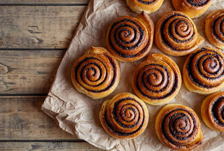 danish: Freshly baked cinnamon buns with spices and cocoa filling on parchment paper. Top view. Sweet Homemade Pastry christmas baking. Close-up. Kanelbule - swedish dessert.