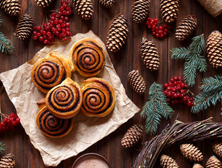 Sweet Homemade christmas baking. Cinnamon rolls buns with cocoa filling. Kanelbulle swedish dessert. Top view. Festive decoration with pine cones and Christmas tree Archivio Fotografico