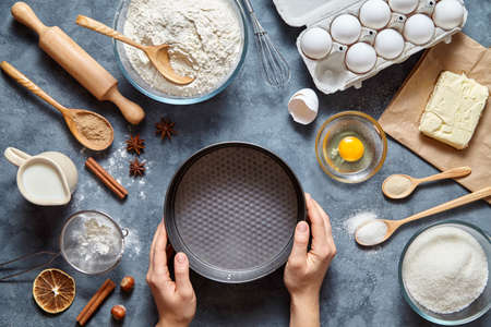 Il processo di fare l'impasto a mano. Torta di cottura in cucina - ingredienti ricetta pasta uova, farina, latte, burro, zucchero sul tavolo. Vista dall'alto. Distesi. Archivio Fotografico - 68464654