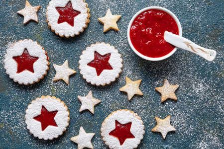 starlike: Round and star-like biscuits ginger cookies with strawberry jam. Flat lay. Traditional Austrian christmas Linzer cookie. Home Useful pastries.Top view. Stock Photo