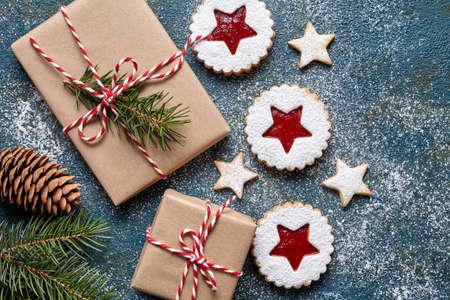 Nieuwjaar of kerstcadeaus omwikkeld met lint Xmas vakantie seizoen viering handgemaakt geschenkdoos en linzer Chrismas koekjes met jam, fir tree kegels op gepoederde vintage tafel achtergrond Stockfoto - 68464126