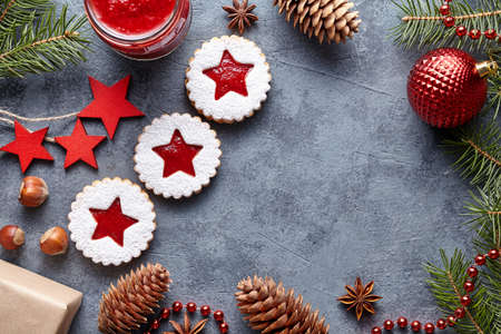 teacake: Linzer star cookies with jam filling traditional Christmas seasonal baked homemade Austrian sweet dessert food Xmas celebration pastry powdered holiday snack on vintage table background. Flat lay Stock Photo