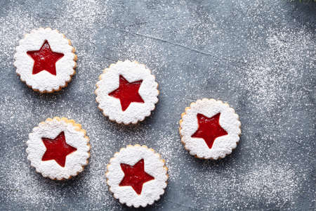 teacake: Linzer star cookies with berry jam filling traditional Christmas homemade decoration Austrian sweet dessert food Xmas celebration pastry powdered holiday snack on vintage table background. Flat lay