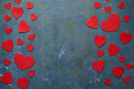 Valentines day background with red woolen hearts on blue concrete creative background with copy space. Valentines day concept. View from above. Flat lay