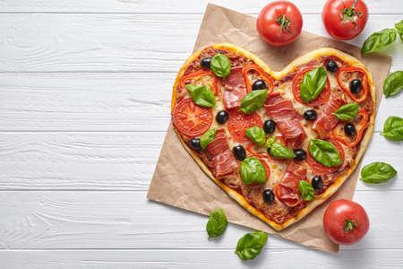 Cuore di pizza a forma di concetto di amore San Valentino design simbolo romantico ristorante per la cena cibo italiano. Prosciutto, olive, pomodori, basilico e pasto mozzarella servito su sfondo bianco tabella Archivio Fotografico - 70370151