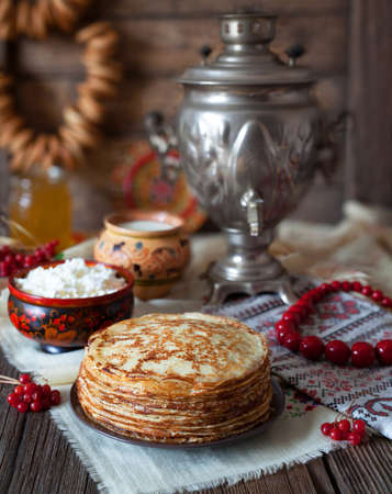 Traditional Ukrainian or Russian pancakes with cottage cheese and milk on vintage wooden table background. Traditional dishes on the holiday Carnival Maslenitsa Shrovetide .