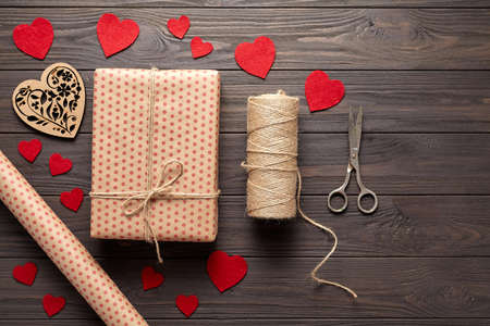 twine: Flat lay Stylish composition with gift, scissors, wrapping paper and twine. Packaging of gifts on Valentines Day, a birthday or Mothers Day. Dark wooden background with hearts. Top view.