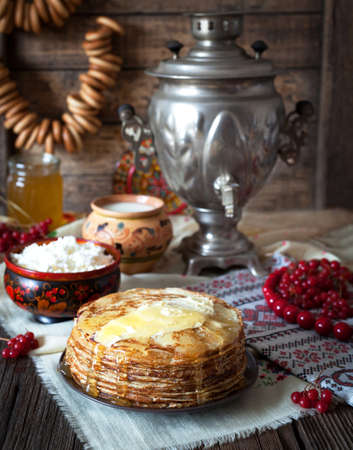 pancake week: Traditional russian pancakes with cottage cheese, milk, butter and sour cream on napkins with embroidery. Traditional dishes on the holiday Carnival Shrovetide Stock Photo