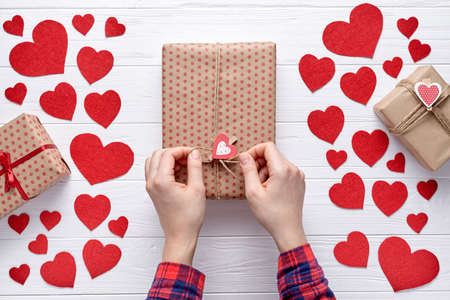 Female hand packed gift and tie a bow on a box of Valentines Day, a birthday or Mothers Day. White wooden background with hearts and gifts. Flat lay.