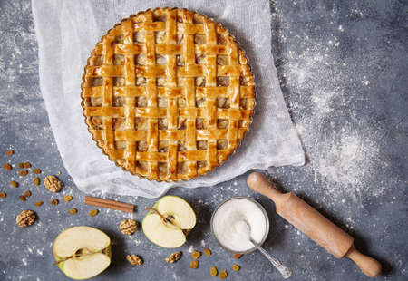 American apple pie delicious tart with nuts and raisins on a concrete background and ingredients of which in turn it is cooked. Flat lay.