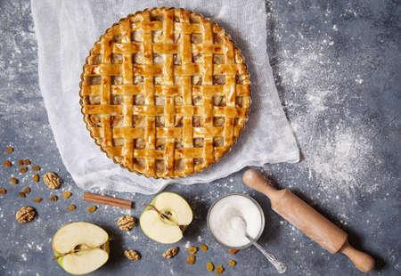 Amerikaanse appeltaart heerlijke taart met noten en rozijnen op een concrete achtergrond en ingrediënten waarvan het op zijn beurt wordt gekookt. Plat leggen. Stockfoto