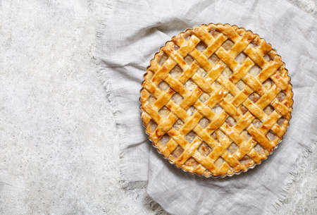 greased: Homemade rustic apple pie preparation greased with egg yolk on white kitchen background. Flat lay. Copy space. Stock Photo