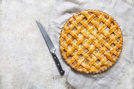 Organic apple pie tart with raisins, nuts and cinnamon on white kitchen background. Flat lay. Copy space.
