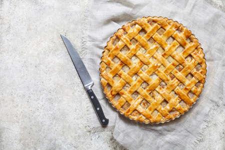 Organische appeltaart scherp met rozijnen, noten en kaneel op witte keukenachtergrond. Plat leggen. Ruimte kopiëren. Stockfoto