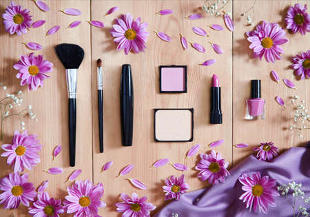 applicator: Set makeup decorative cosmetics in shades of purple on a wooden background decorated with spring flowers. Blush, powder, eye shadow, makeup brushes, nail polish. Flat lay. Top view. Stock Photo