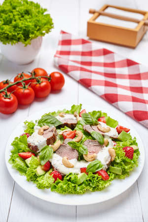 Spring salad with strawberries, avocados, spinach, beef, cashews and white sauce.. Low carb diet. White restaurant a wooden background.