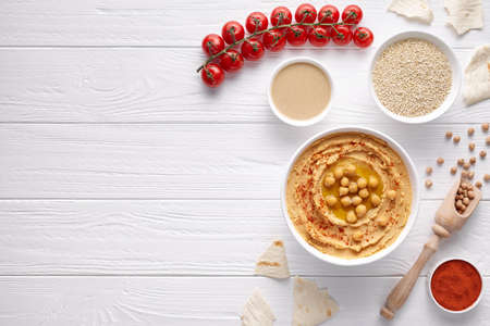 Hummus traditional snack in bowl lebanese arabic appetizer chickpea snack with tahini, sesame, paprika, chick peas and pitta bread. Healthy vegetarian nutrition food