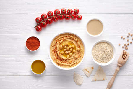 Homemade hummus traditional rustic healthy vegan dip chickpeas paste snack flat lay with natural ingridients, tahini, paprika, olive oil, pitta on table. Healthy vegetarian diet nutrition protein food Stock Photo
