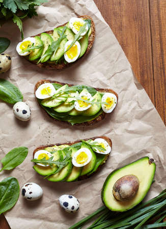 quail: Sandwich, toast with avocado, spinach, guacamole and quail eggs on parchment and dark wooden table. Healthy breakfast lunch concept. Flat lay food composition.
