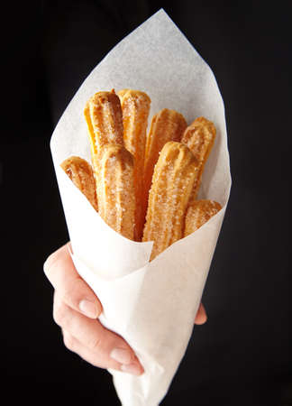Churros traditional Spain or Mexican street fast food baked sweet dough snack in hand cone of parchment paper