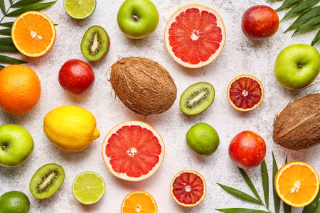 Citrus fruits background flat lay, helthy vegetarian organic food, antioxidant detox nutrition diet. Tropical summer assortment mix grapefruit, coconut, orange, apple, mandarin, sliced kiwi fruit Stock Photo