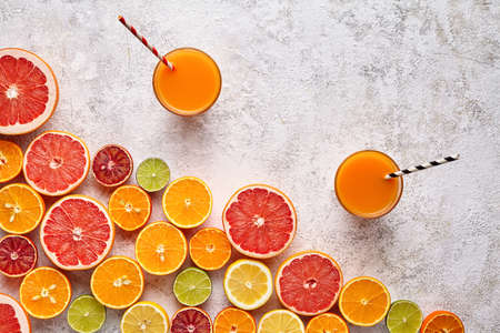 Fresh juice or smoothie vitamin c nutrition drink in citrus fruits background flat lay, healthy lifestyle natural organic detox diet beverage. Tropical summer assortment grapefruit, orange, apple mix