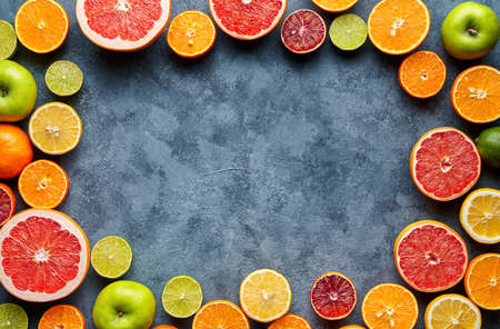 Citrus fruits sliced mix frame flat lay on blue concrete background blank copy design space, healthy vegetarian organic food, antioxidant detox diet. Tropical summer mix grapefruit, orange, apple mix Imagens