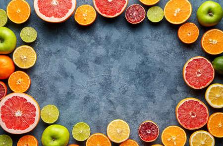 Gesneden de mengelings van de citrusvruchten gesneden vlakte legt op blauwe concrete ruimte van het achtergrond lege exemplaarontwerp, gezonde vegetarische natuurvoeding, anti-oxyderend detoxdieet. Tropische zomermix grapefruit, sinaasappel, appelmix