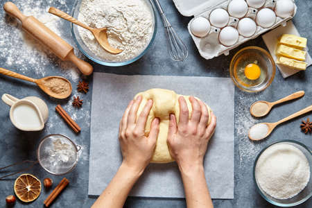 ingridients: Baker chef preparing homemade dough bread, pizza or pie recipe ingridients, food flat lay on kitchen table background. Hands working with butter, milk, yeast, flour, eggs, bakery cooking. Top view