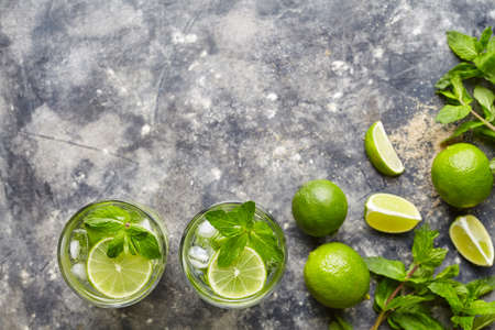 Mojito cocktail non alcohol bar refreshment drink top view copy space two highball glass, summer tropical vacation beverage with rum, citrus slice, mint, lime, soda water and ice on concrete table. Stock Photo