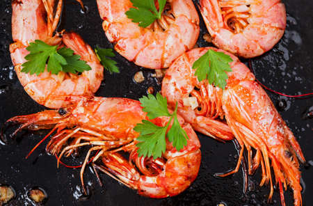 Grilled shrimps on black background. Delicious seafood appetizer served boiled or grilled with spices. Close up. Top view. Stock Photo - 79518634