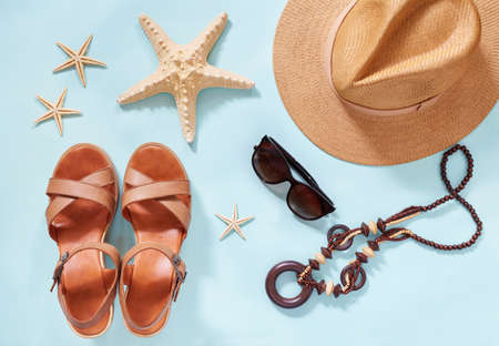 Summer holiday background, flat lay beach womens accessories: straw hat, bracelets, leather sandals, sun glasses, beads and sea stars on blue table. Vacation and travel items. Top view. Stockfoto