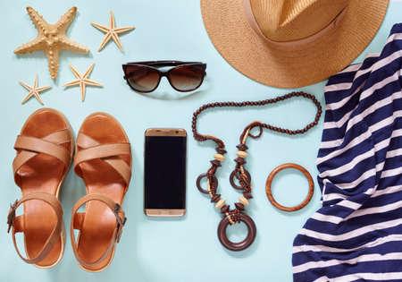 Estate donna moderno stile di vita accessori di abbigliamento alla moda per le vacanze di viaggio: cappello, bracciali, occhiali da sole, perline, vestito, smartphone dorato. Piatto fondo blu. Copia spazio per testo.