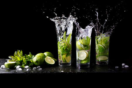 Mojito summer beach refreshing tropical cocktail splash in glass highball alcohol drink with soda water, lime juice, mint leaves, sugar, ice and rum. Dark black background with copy space text