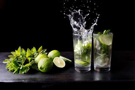 Mojito traditionele strand verfrissende cocktail alcohol drinken in glas met splash, bar voorbereiding soda water, limoen, muntblaadjes, suiker en rum. Donkere zwarte achtergrond met kopie ruimte voor tekst Stockfoto