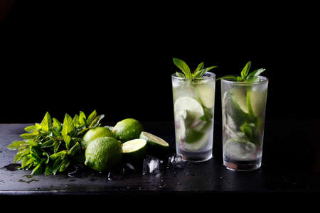 Mojito traditional summer refreshing cocktail alcohol drink in glass, bar preparation soda water beverage, lime juice, mint leaves, sugar, and rum. Dark black background with copy space for text