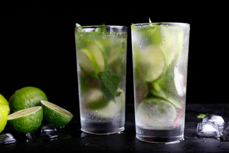 Mojito traditionele zomer vakantie verfrissende cocktail alcohol drinken in highball glas, frisdrank water drank, limoensap, muntblaadjes, suiker en rum. Donkere zwarte achtergrond met kopie ruimte tekst