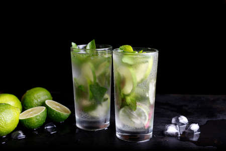 Mojito zomervakantie verfrissende tropische cocktail alcohol drinken in highball glas, frisdrank water drank, limoensap, muntblaadjes, suiker en rum. Donkere zwarte achtergrond met kopie ruimte tekst