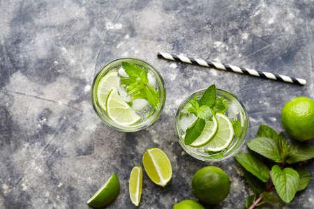 Mojito Cuba highball cocktail non-alcoholisch drankje, zomerse tropische vakantie drank met rum, pepermuntmunt, limoensap, frisdrank water, suiker en crushed ijs op concrete achtergrond