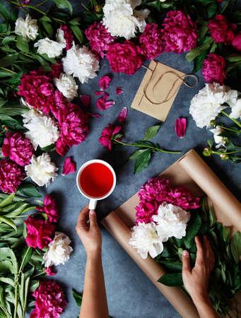 Bloemist op het werk. Een vrouw in het proces van het maken van een zomerboeket van pioenen houdt in haar hand een kop theekaarkade. Hulpmiddelen en accessoires bloemisten moeten een boeket opmaken.