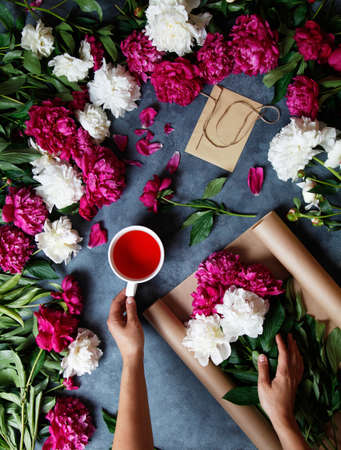 Florist at work. A woman in the process of making a summer bouquet of peonies, holds in her hand a cup of tea karkade. Tools and accessories florists need for making up a bouquet.