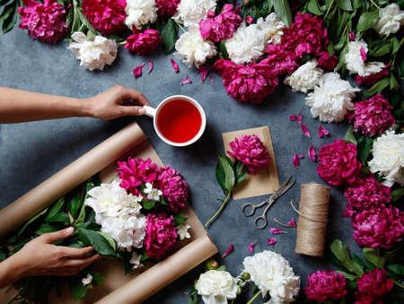 Hulpmiddelen en accessoires die bloemisten nodig hebben om een boeket van pioenen te maken: kraftpapier, schaar, touw, een envelop op tafel. Bloemist op het werk. Uitzicht van boven. Plat leggen. Karkade-thee. Stockfoto