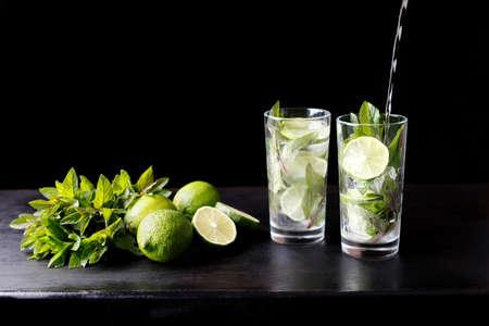 Mojito traditionele strand verfrissende cocktail alcohol drinken in glas bar voorbereiding gieten soda water, limoen, muntblaadjes, suiker en rum. Donkere zwarte achtergrond met kopie ruimte voor tekst