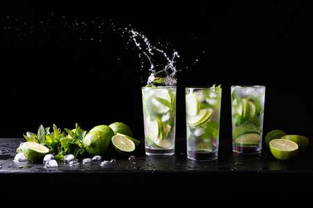 Drie glazen verfrissende Mojito-rumalcoholcocktail op de bar, plonsen in een glas. Feestcocktail. Kalk, ijs en munt op tafel. Zwarte achtergrond. Ruimte voor tekst kopiëren. Stockfoto
