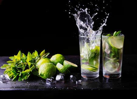Verfrissende zomerse cocktail mojito limonade met spatten. Partycocktail. Kalk, ijs en munt op de tafel. Zwarte achtergrond. Detailopname. Ruimte voor tekst kopiëren.