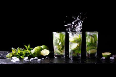 Mojito zomerfeest verfrissende tropische cocktail non-alcoholische drank in highball glas met splash soda water, limoensap, muntblaadjes, suiker, ijs en rum. Donkere zwarte achtergrond met kopie ruimte tekst